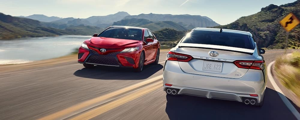 Red and white 2019 Toyota Camry sedans on the road