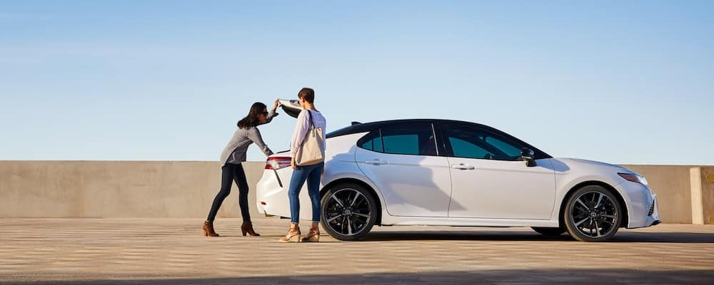 Women opening trunk of white 2019 Toyota Camry in profile