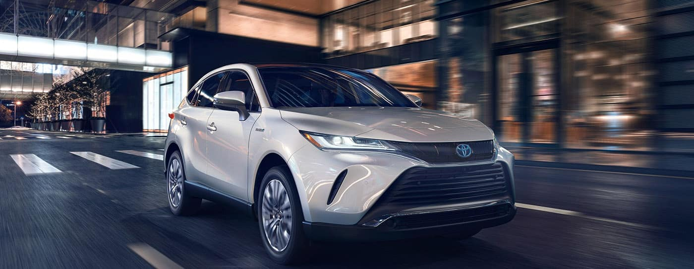 New 2021 silver Toyota Venza driving in the city.
