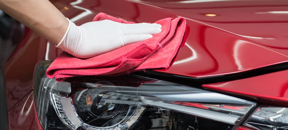 Hand drying the front of a red car