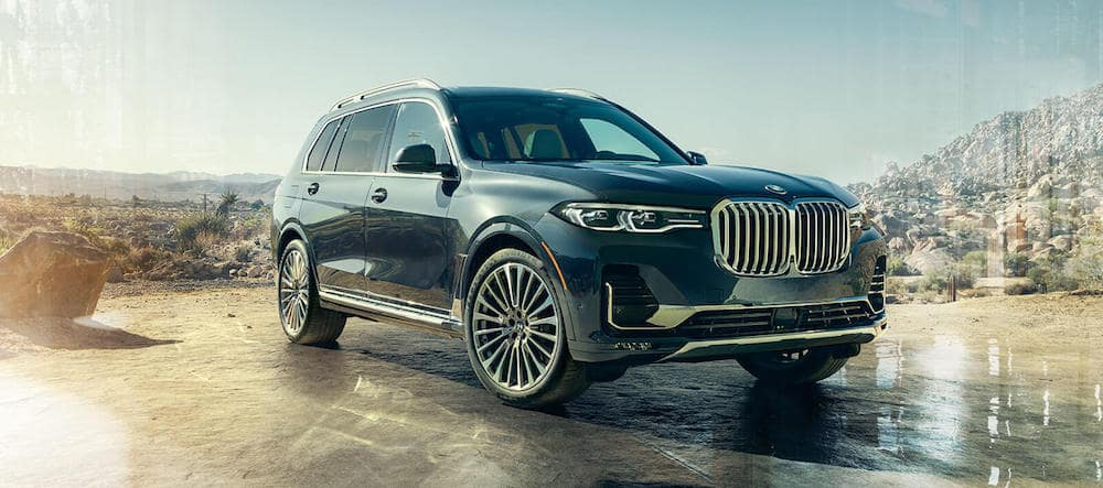 A 2020 BMW X7 parked in the desert in front of a mountain