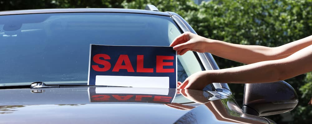 woman placing sale sign on car windshield