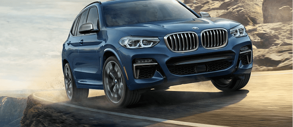 Blue BMW SUV on a Dirt Road
