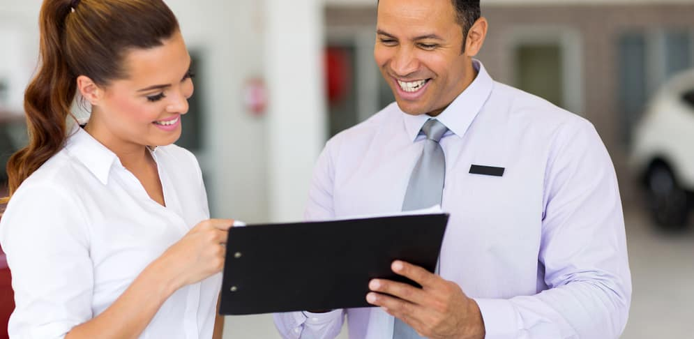 Car Salesman Reviewing Contract With Customer