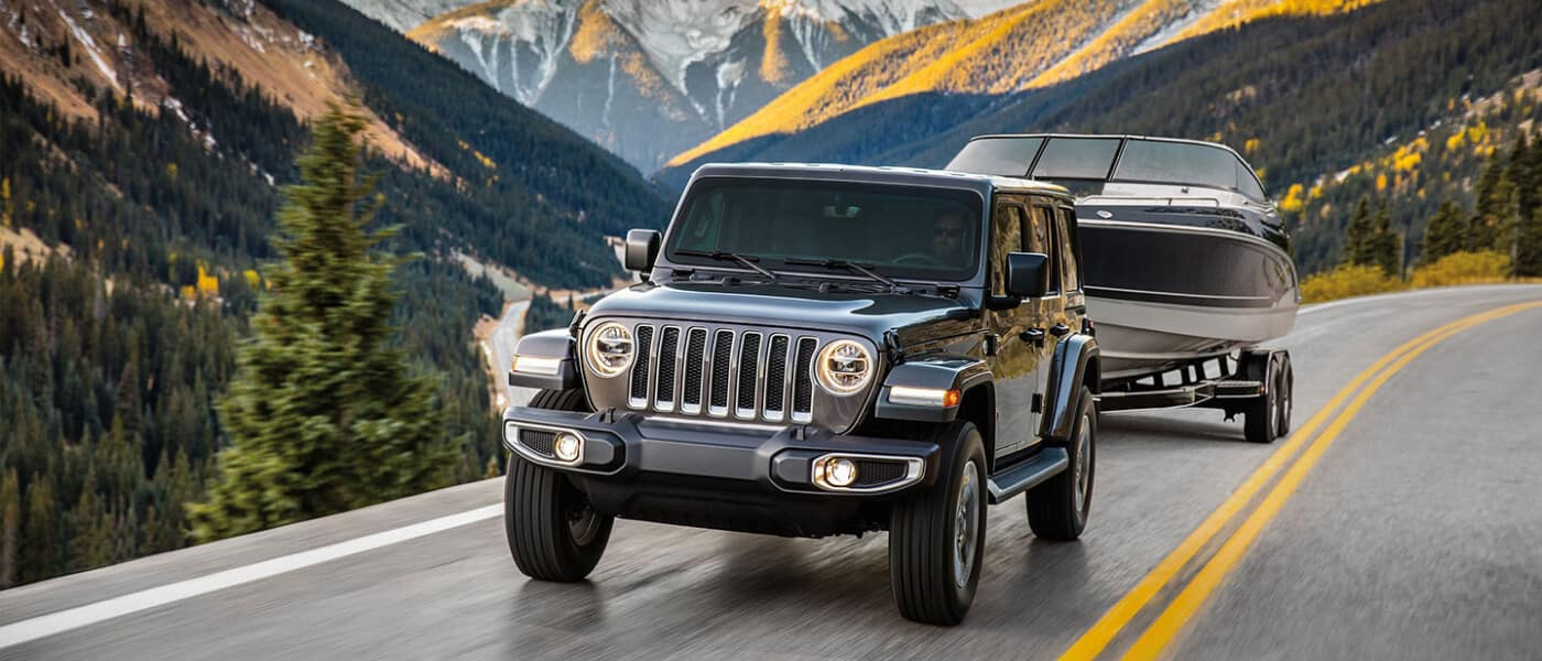 2020 Jeep Wrangler exterior towing boat in mountain
