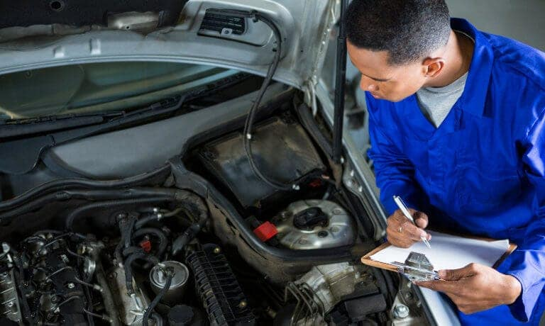 Certified Service Technician inspecting under hood of vehicle