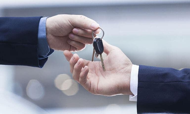 Car dealer handing keys over to new owner