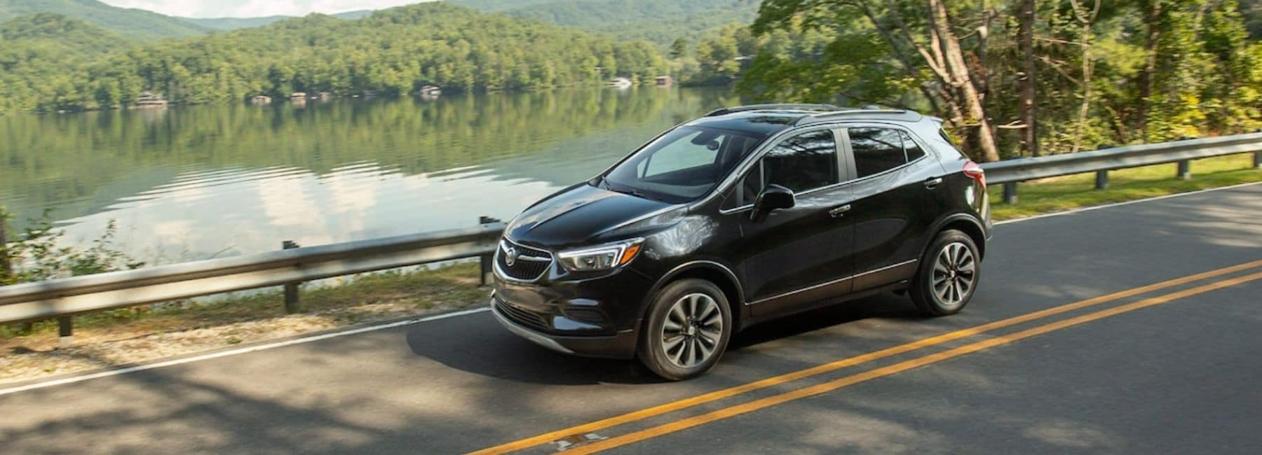 Black 2021 Buick Encore Driving With A Lake Background