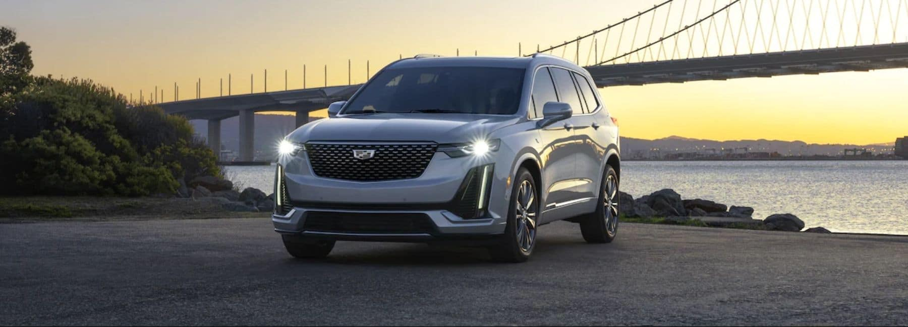 Silver 2021 Cadillac XT6 With Water and Bridge in Background - Cadillac Dealer Near Roswell, NM