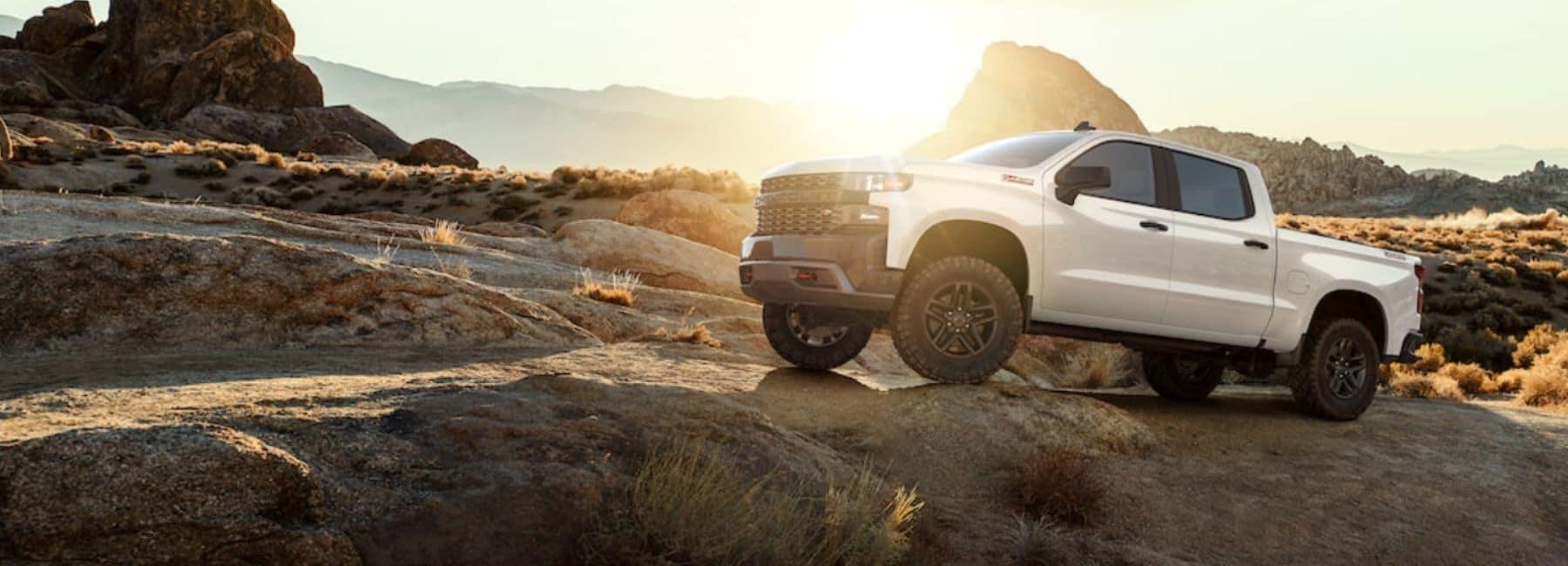 White 2021 Chevrolet Silverado Climbing Rocks In Desert With Sun In Background   Chevrolet Dealer Near Hobbs, NM