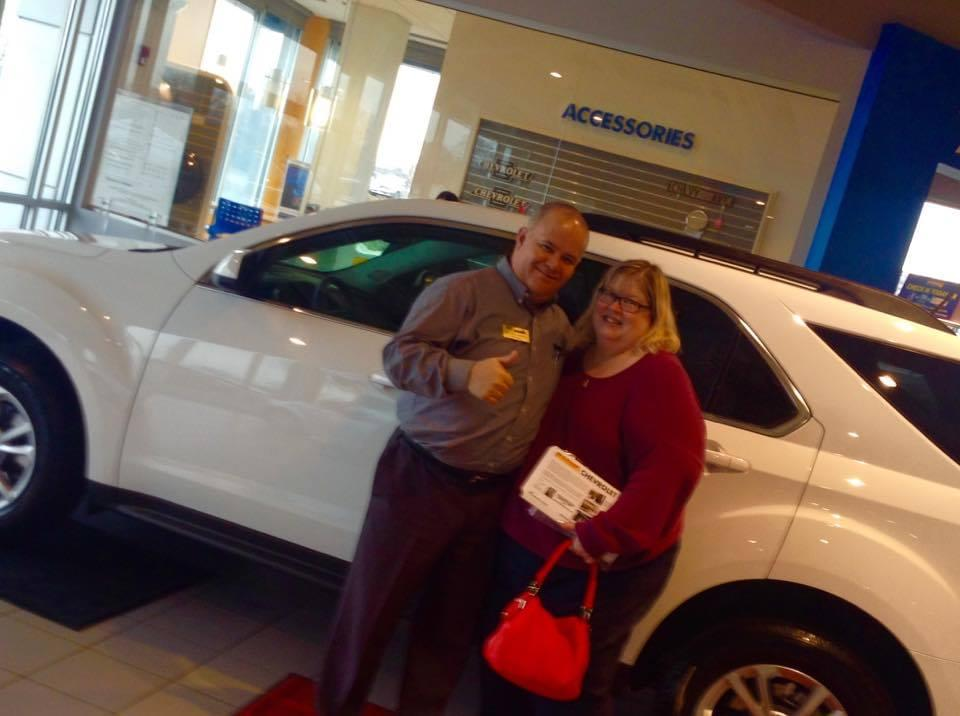 Customer standing and smiling with dealership employee in front of vehicle at Sunrise Chevrolet dealership