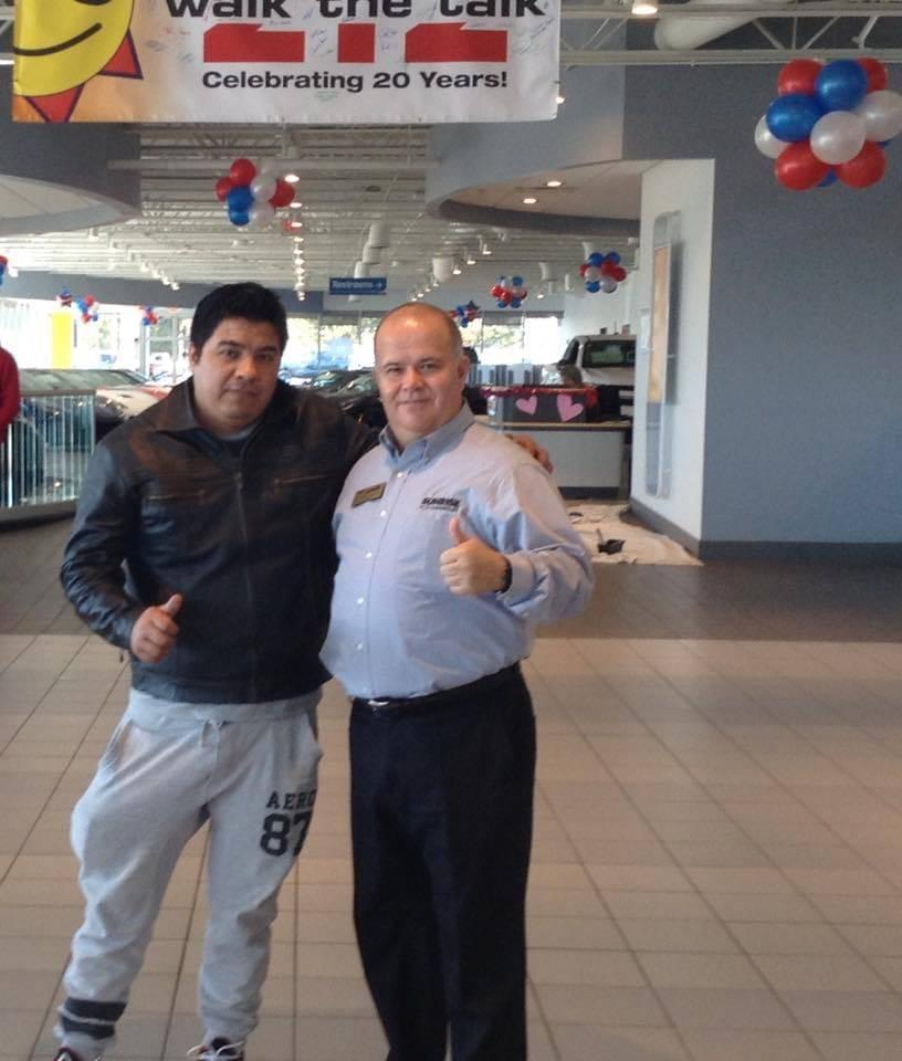 Customer standing and smiling with dealership employee at Sunrise Chevrolet dealership