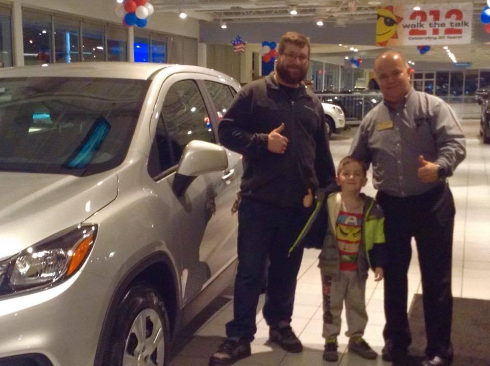 Customers standing and smiling with dealership employee in front of vehicle at Sunrise Chevrolet dealership