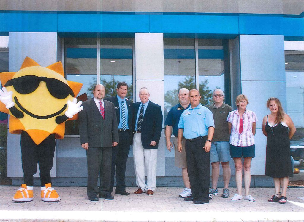 Crowd of people standing with Sunrise Chevy mascot in front of the dealership