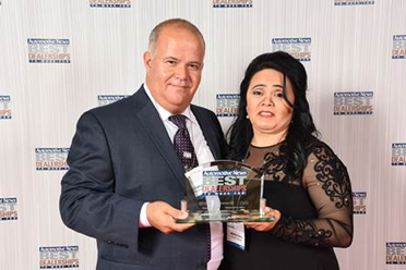 Two people holding Best Dealerships award
