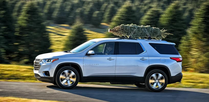 Christmas Tree Tied To the Top of a Chevrolet Vehicle