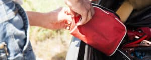 Man removing emergency preparedness kit from back of car