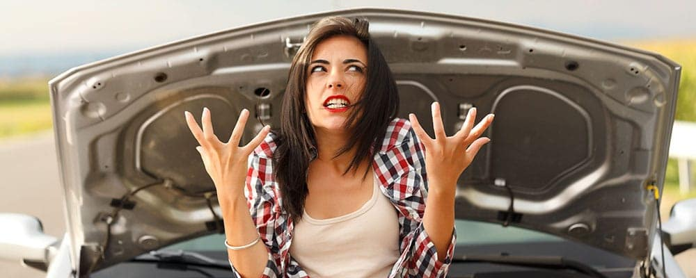 Woman being very angry because of her car's failed engine 32351119