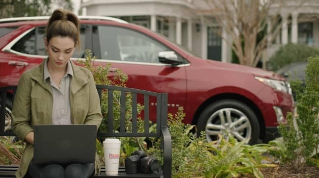 woman on laptop with chevy suv in background