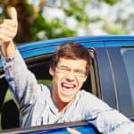 Boy smiling through a car window.