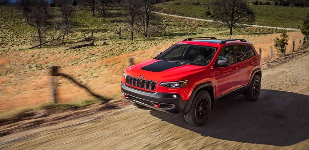 Red 2019 Jeep Cherokee Driving on Dirt Road