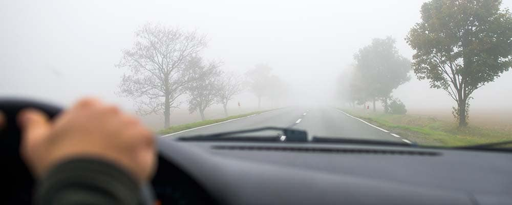 Car driving in fog