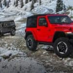 Two Jeep Wranglers parked on a snowy mountain