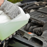 Mechanic adds coolant to engine