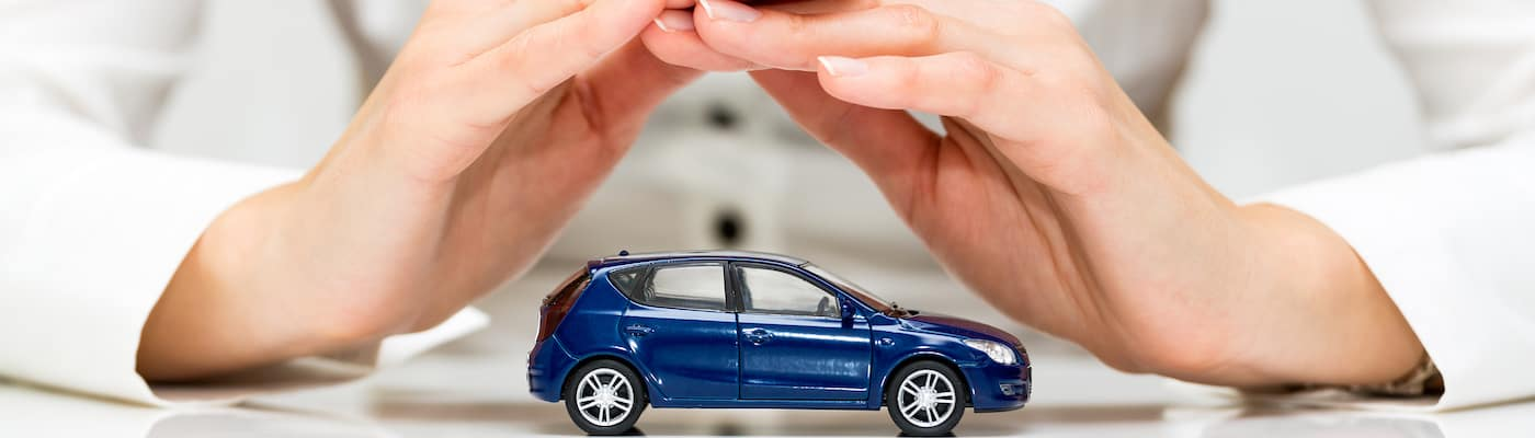Hands protecting a model car