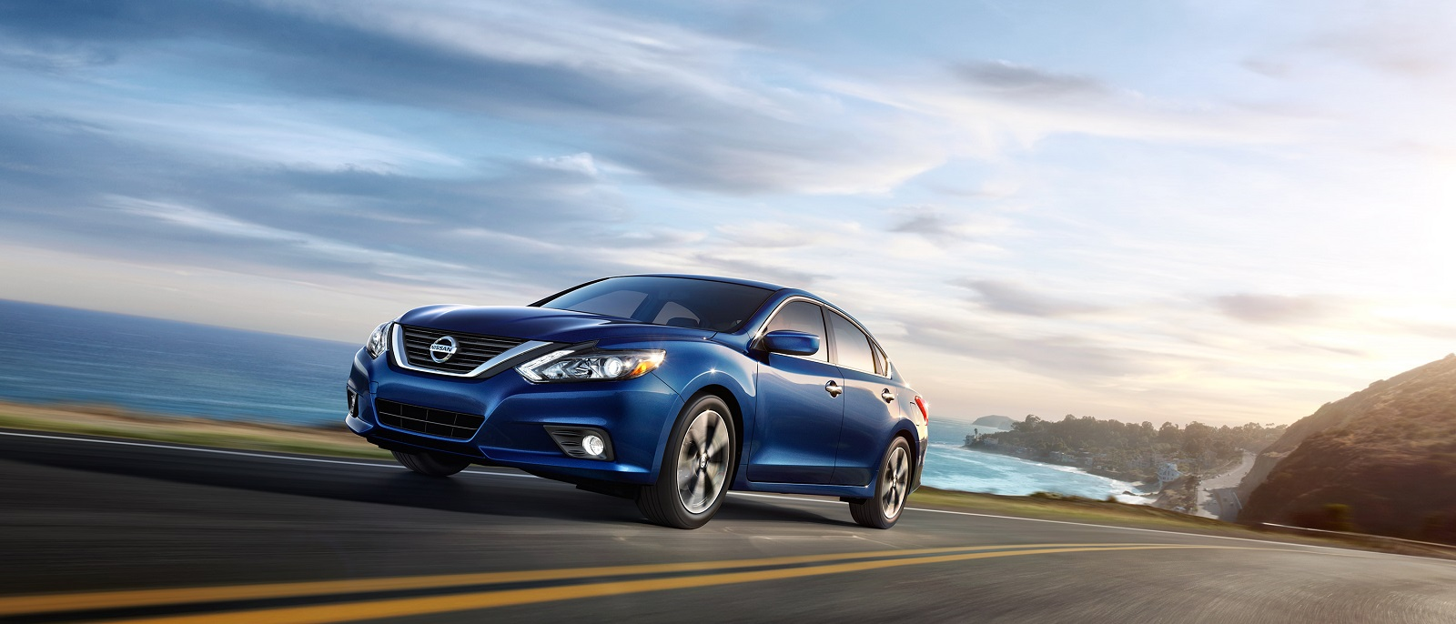 2016-nissan-altima-driving-ocean-highway-deep-pearl-blue
