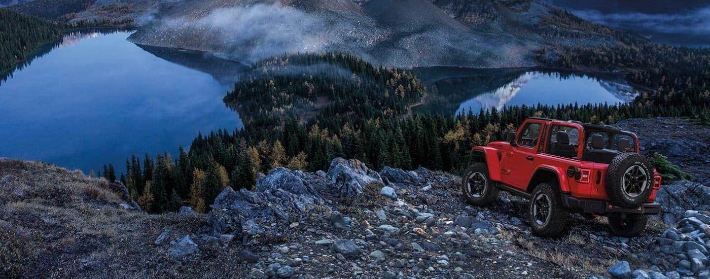 A red 2020 Jeep Wrangler with no top or doors is parked on top of a mountain overlooking a lake.