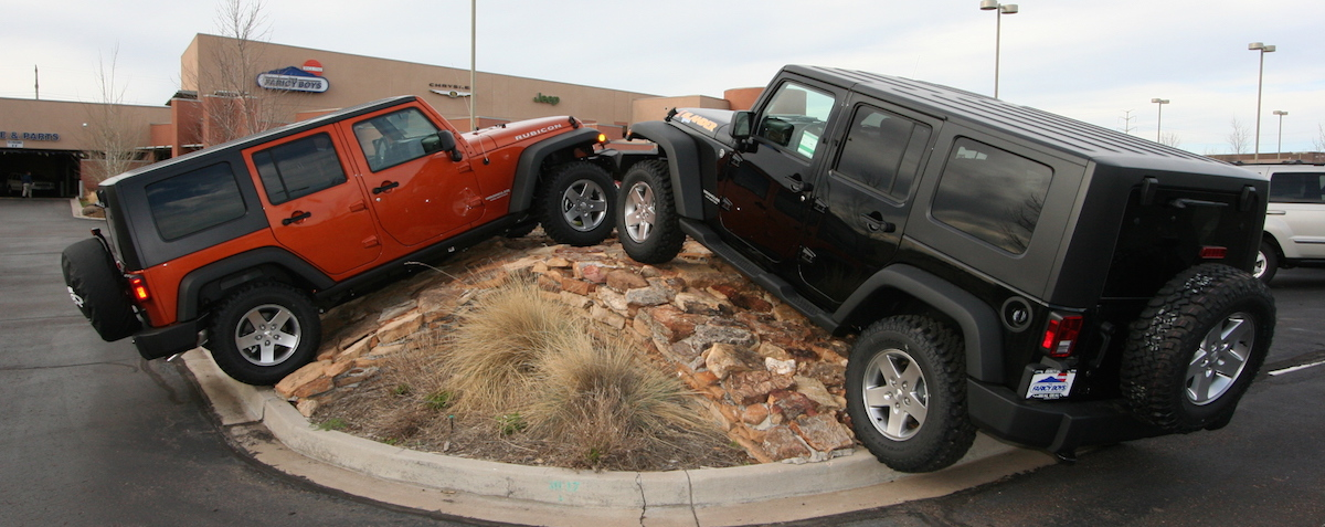 A red and a black Jeep Wrangler Unlimited are climbing a rock pile in front of The Faricy Boys dealership in Colorado Springs.