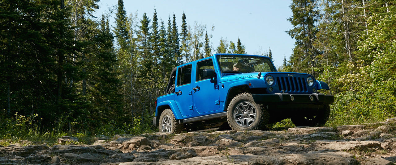 Blue 2016 Jeep Wrangler driving through the woods rock crawling