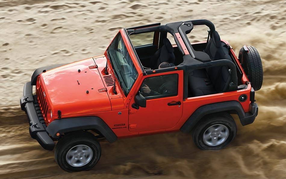 A red 2014 used Jeep Wrangler with no top is shown from above driving on sand.