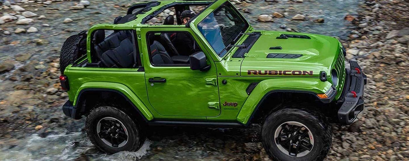 A popular used Jeep Wrangler for sale, a green Wrangler Rubicon with no top is crossing a river.