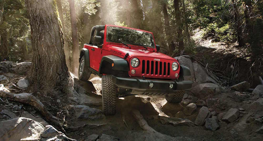 A red 2014 used Jeep Wrangler is climbing over rocks on a forest trail.