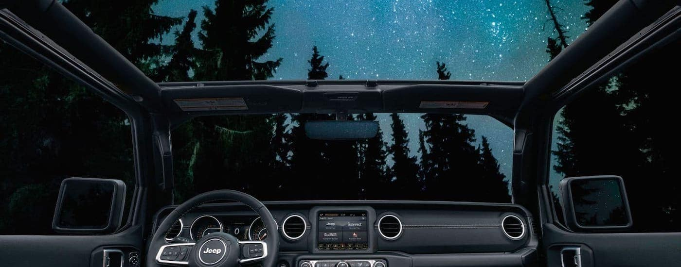 A starry night sky is shown from the interior of a used Jeep Wrangler in a forest.