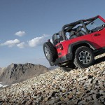A red Used Jeep Wrangler with not top is climbing a rocky hill outside Colorado Springs.