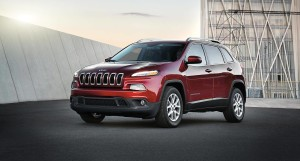 A red 2016 Jeep Cherokee is parked in front of a modern building in Colorado Springs, CO.