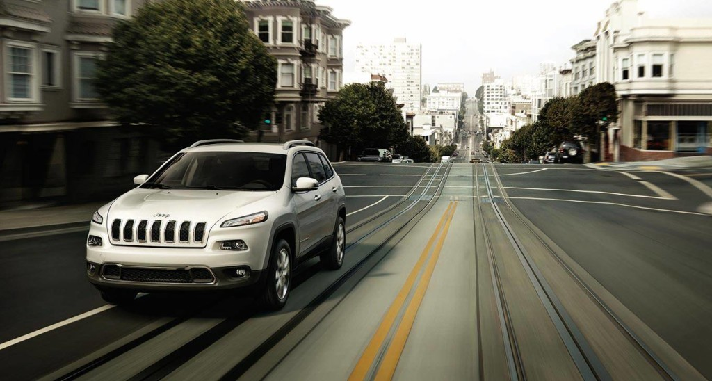 A white 2016 Jeep Cherokee is driving on a city street.