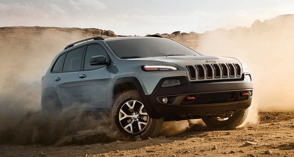 A gray 2016 Jeep Cherokee Trackhawk is kicking up dirt in a field.