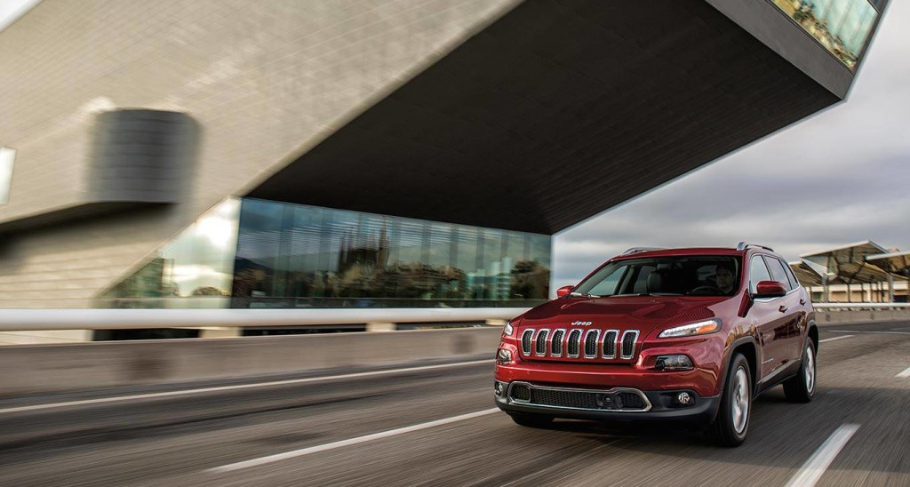 A red 2016 new Jeep Cherokee is driving on a highway.