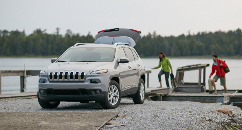 A couple is getting off a boat and loading cargo into the rear of a silver 2016 Jeep Cherokee at a river bank.