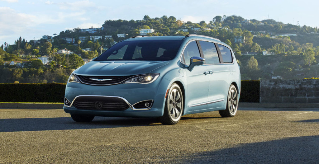 A light blue 2017 Chrysler Pacifica Hybrid is in a parking lot in front of a hill.