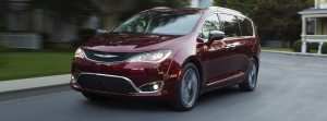A dark red 2017 Chrysler Pacifica is driving on a suburban street near Colorado Springs.