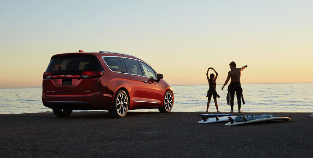 Two surfers are next to a red 2017 Chrysler Pacifica that is parked at the ocean.