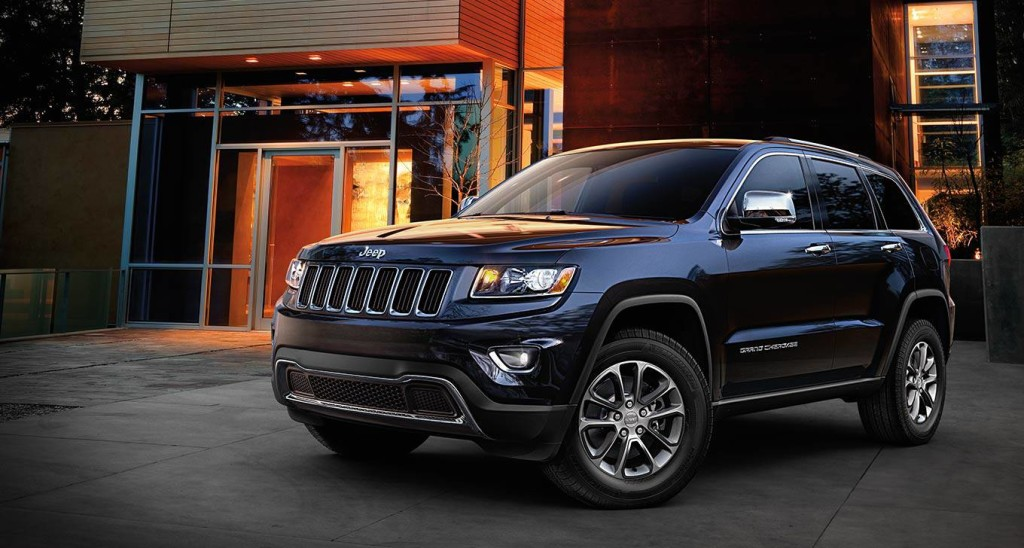 A black 2016 Jeep Grand Cherokee Limited is parked in front of a building at night.