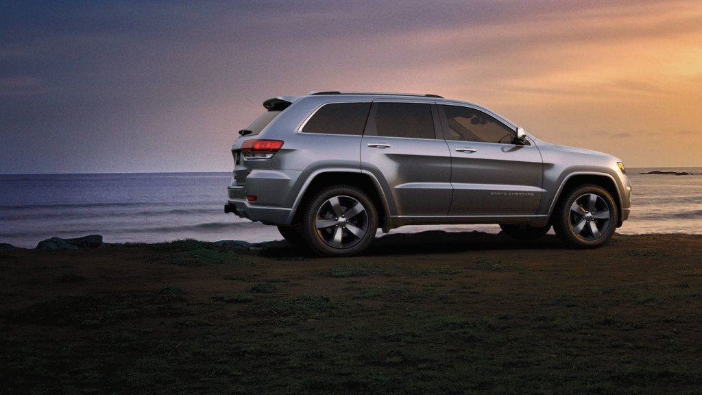 A silver 2016 Jeep Grand Cherokee Overland is parked on a beach at sunset.