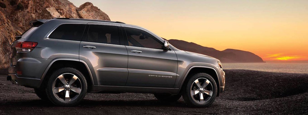 A gray 2016 Jeep Grand Cherokee is parked on a beach watching the sunset.