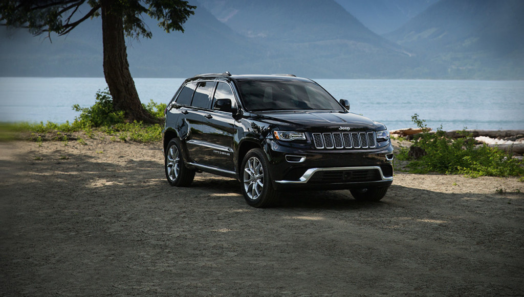 A black 2016 Jeep Grand Cherokee Summit is parked in front of a lake and mountains.